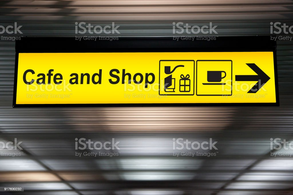 sign cafe and shop with arrow for direction for passenger to buy food , drink and shopping. yellow cafe and shop sign at the airport stock photo