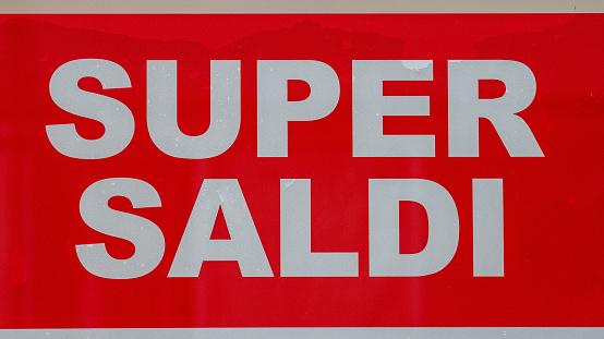 sign displayed on a shop window that reads super sales
