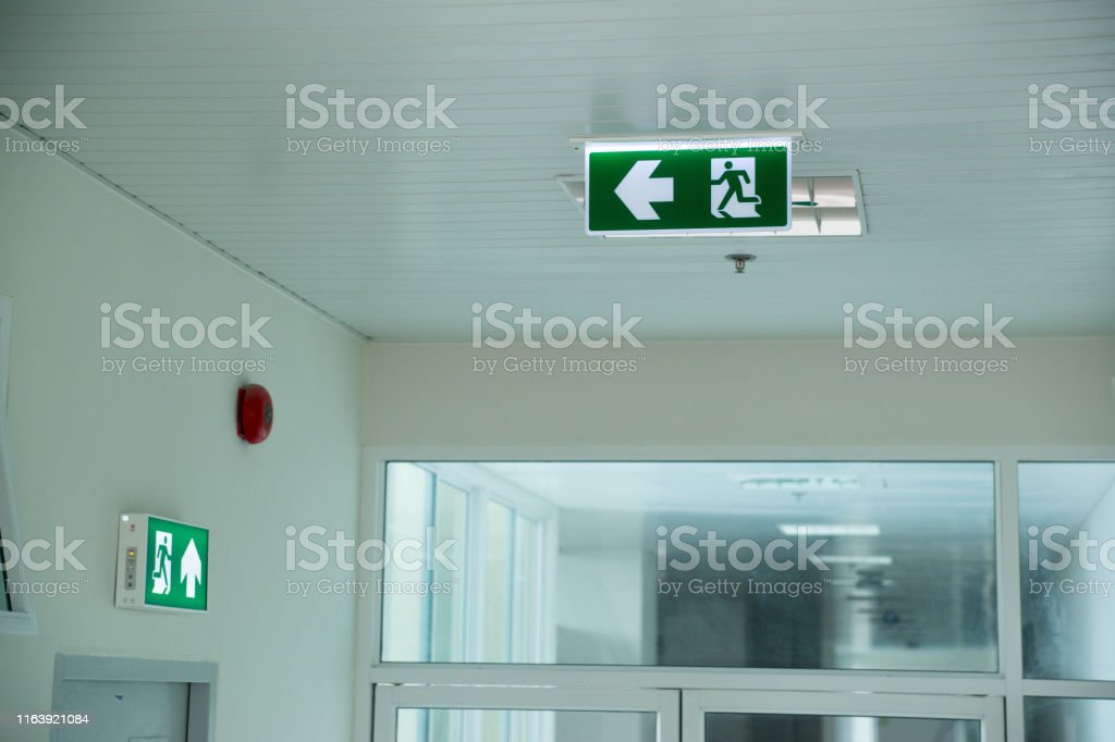 Emergency exit sign at path way indoor building public facility that...