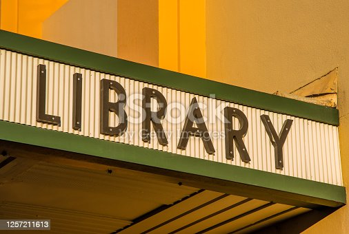 A sign for a public library in green lettering on a yellow corrugated iron marquee, and yellow concrete wall