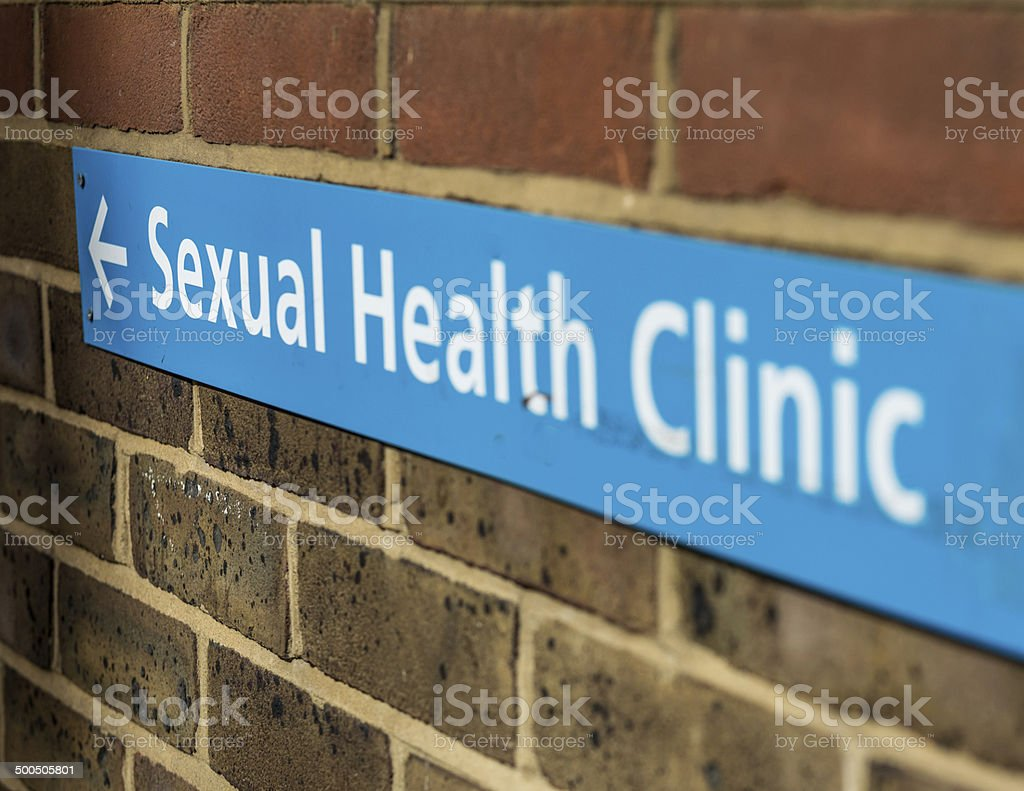 Sign for a sexual health clinic on a brick wall stock photo