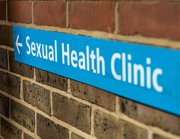 Sign for a sexual health clinic on a brick wall Sign for a sexual health clinic. sexually transmitted disease stock pictures, royalty-free photos & images