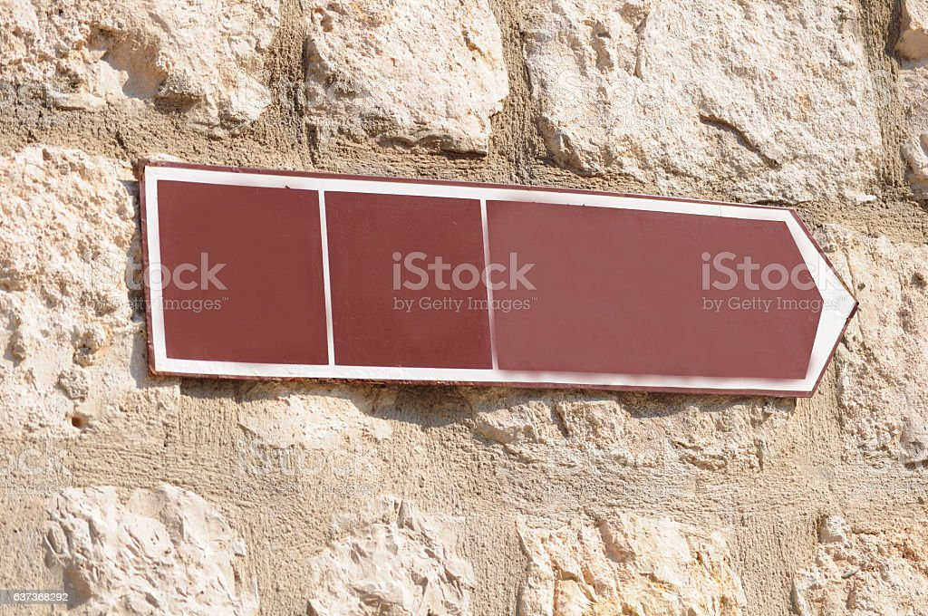Sign for direction on stone wall stock photo