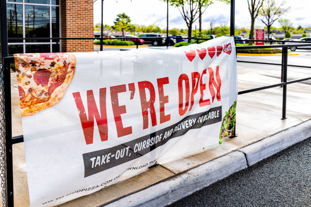 Sign for open pizza restaurant for take-out curbside and delivery during coronavirus Covid-19 epidemic Herndon, USA - April 27, 2020: Virginia Fairfax County street with sign for open pizza restaurant for take-out curbside and delivery during coronavirus Covid-19 epidemic curbsidepickup stock pictures, royalty-free photos & images
