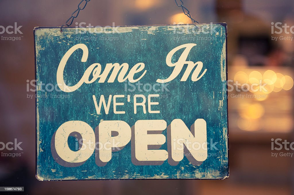 Sign hanging from a chain that says Come In we're Open royalty-free stock photo