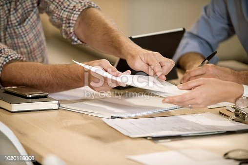 Business professional showing the place to sign on the document to female colleague. Close-up for business people signing a contract paper.