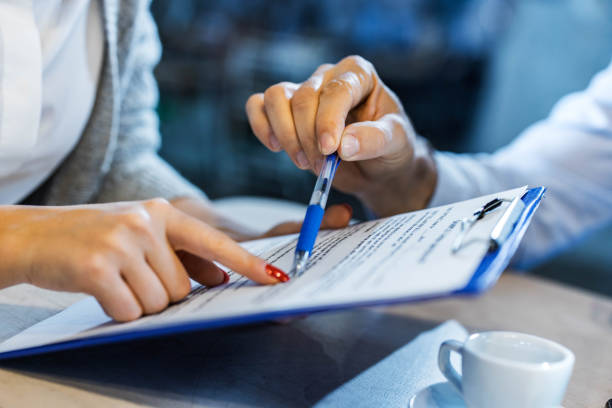 Sign here! Close up of unrecognizable insurance agent showing his customer where to sign the contract. mortgages and loans stock pictures, royalty-free photos & images