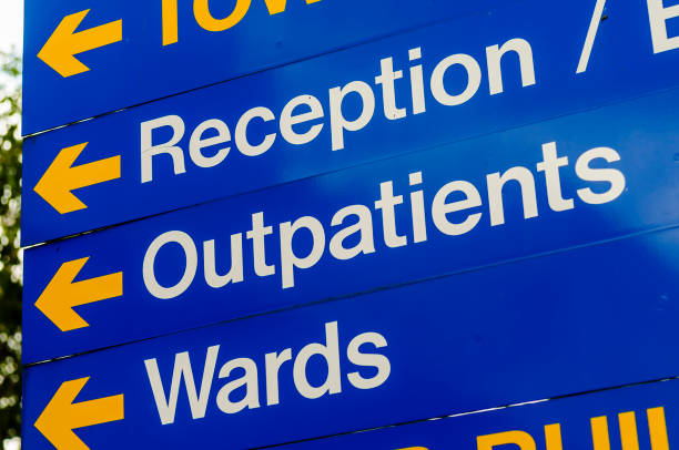 Sign in a hospital directing visitors to reception, outpatients and wards. Sign in a hospital directing visitors to reception, outpatients and wards. outpatient stock pictures, royalty-free photos & images