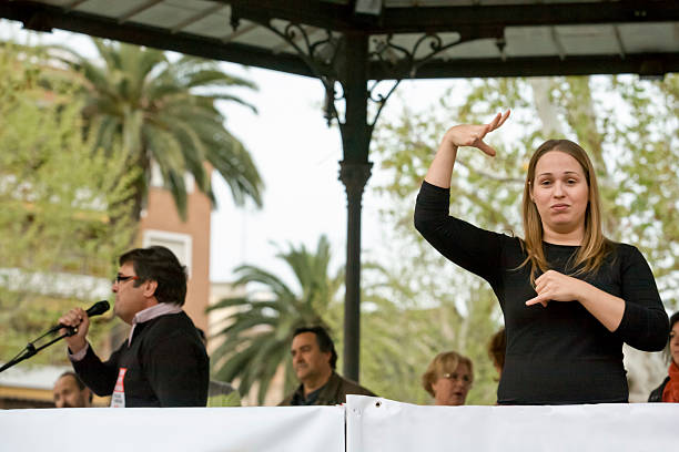 sign language woman interpreter gestures during a meeting - sign language stock photos and pictures