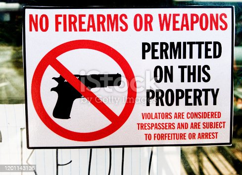 A sign illustrated with a crossed-out gun firmly states