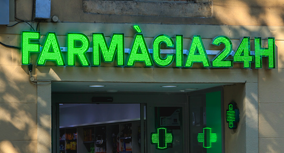 sign of a small Spanish pharmacy in a residential area of Barcelona