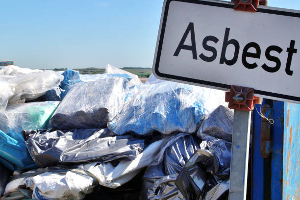 sign of german word Asbest. waste of asbestos on dump site. Waste Disposal concept for consumerism, modernization,  environmental crisis and toxic-waste. Scrapyard scenery. stock photo