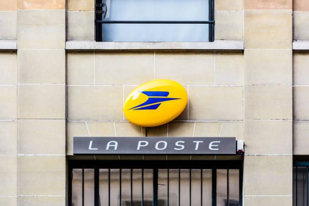 Signe de La Poste, la compagnie des services postaux français, au-dessus de l'entrée d'un bureau de poste. - Photo