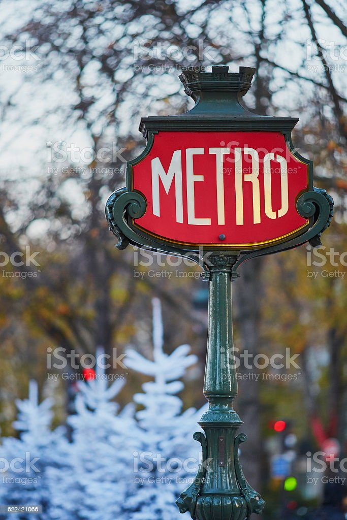 Sign of Parisian underground with Christmas trees covered with snow stock photo