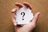 istock Sign of question cards in the woman's hand on the table. Solution search concept. 913689720