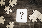 istock Sign of question with puzzle on the wooden background. Solution search concept. 867685278