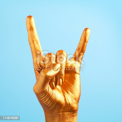 gold painted hand making sign of the horns