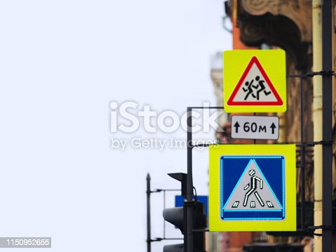 istock Sign of the pedestrian crossing on a city street, blurred background. Sign Carefully children 1150952655