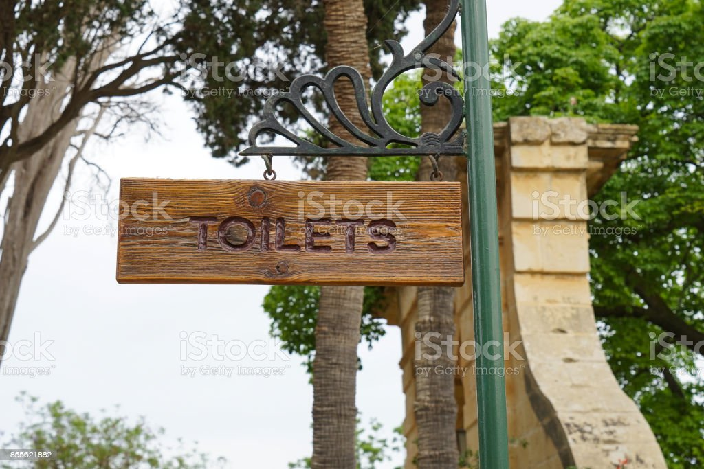Sign of toilet written on a wooden board. Mark public toilet in the park. stock photo