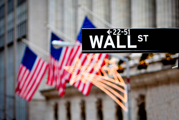 sign of wall street with flags in the background - wall street lower manhattan stock pictures, royalty-free photos & images