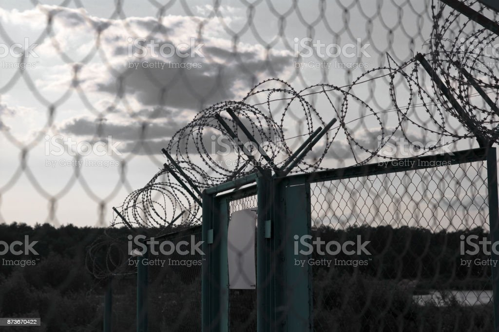sign on a fence with barbed wire stock photo
