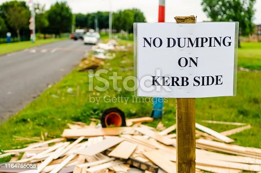 A sign on a grass verge warning people not to dump rubbish on the kerb side, with a lot of discarded wood, rubbish and other items littering the ground.
