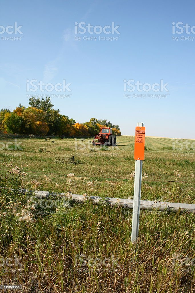 sign on farm land says 'caution buried fiber optic cable' royalty-free stock photo