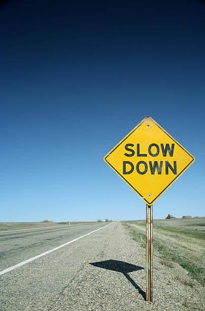 sign on flat prairie road warns drivers to slow down - langzaam stockfoto's en -beelden