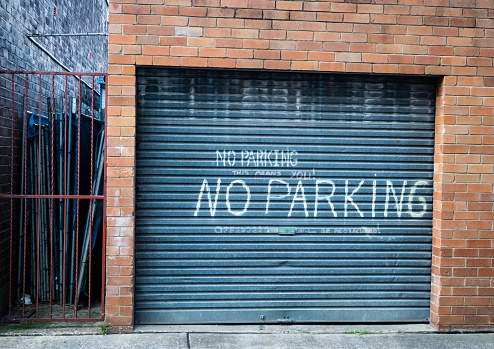 Sign on garage door in laneway near gate saying NO PARKING THIS MEANS YOU