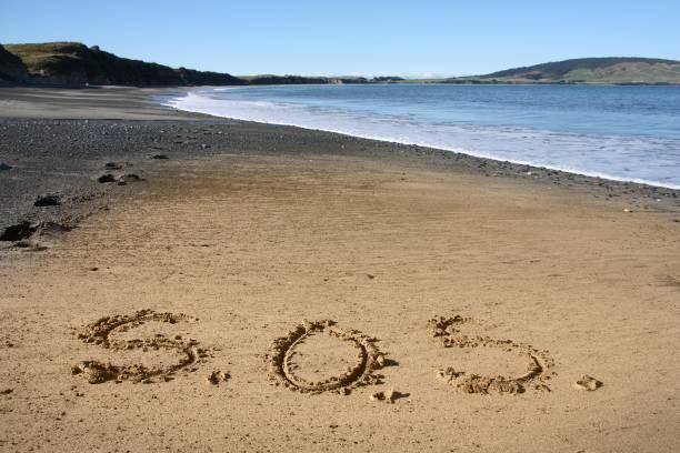 SOS-Zeichen auf Sand – Foto