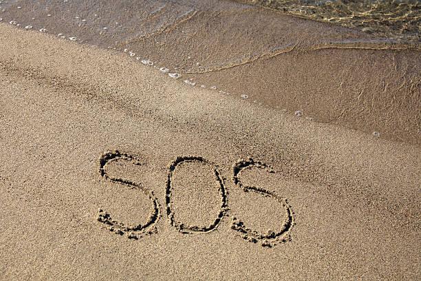 sos sign on sandy beach - rettungsinsel stock-fotos und bilder