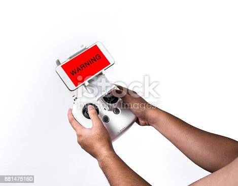 istock WARNING sign on screen, Men hold a drone Remote control with smart phone on white background, isolated. 881475160