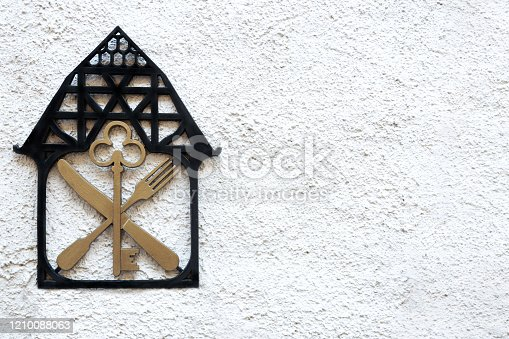 A sign on the wall with the image of the house key knife and fork