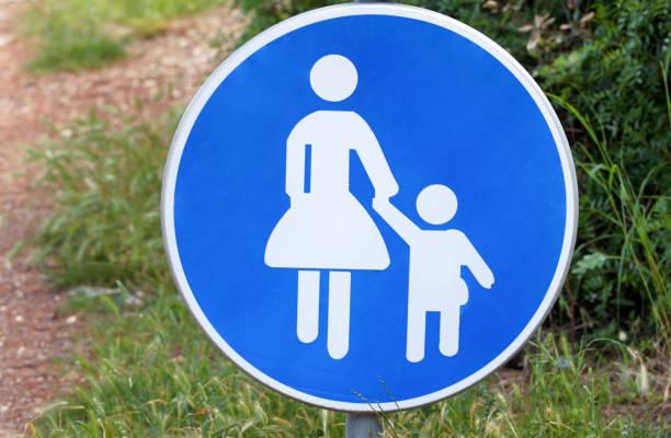 Sinal ou símbolo para pedestres. Sinal de estrada de bebê sinal azul tomar cuidado quando atravessar o símbolo da estrada. Sinal de tráfego de pedestres na natureza. Sinal de pedestre. Sinais de aviso e proibidos. - foto de acervo