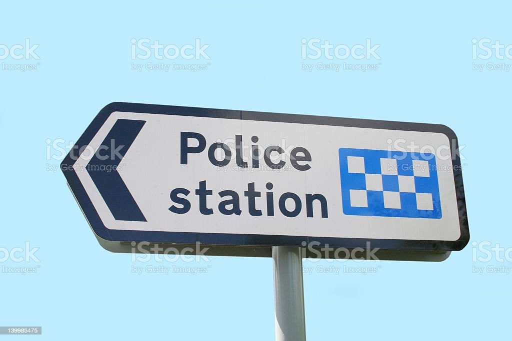 Sign pointing towards the police station stock photo