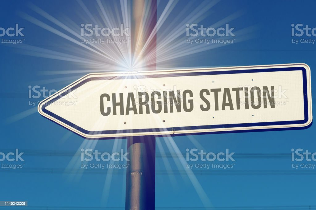 A Sign Points Towards A Charging Station For Electric