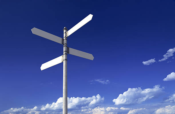 Sign post with four blank signs on a blue sky stock photo