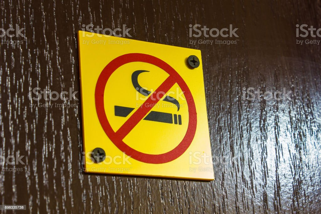 A sign prohibiting smoking on the door stock photo