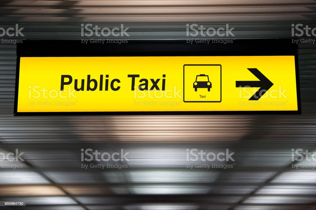 sign public taxi with arrow to direction for passenger to taxi park at the airport terminal. taxi and transportation service concept. stock photo