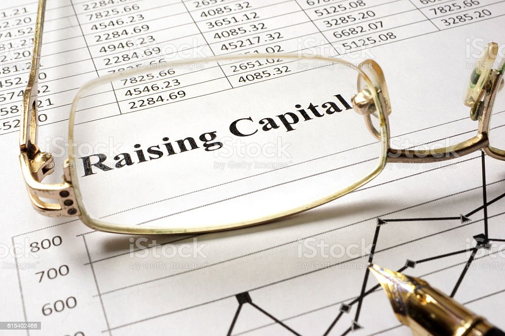 Sign raising capital on a paper and glasses. stock photo