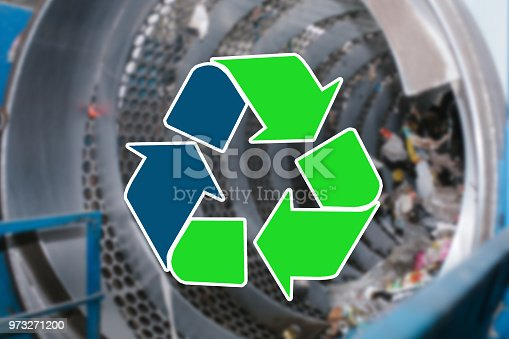 istock Sign recycling waste. The waste sorting and processing plant is blurry in the background 973271200
