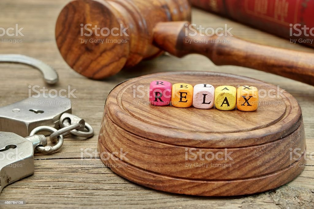 Sign Relax on the Soundboard, Judges Gavel, handcuffs and book stock photo
