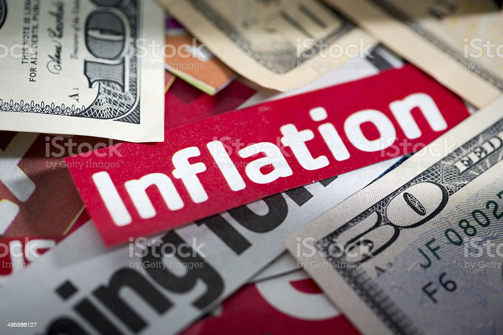 Sign saying 'inflation' on pile of US banknotes. It's depressing! stock photo