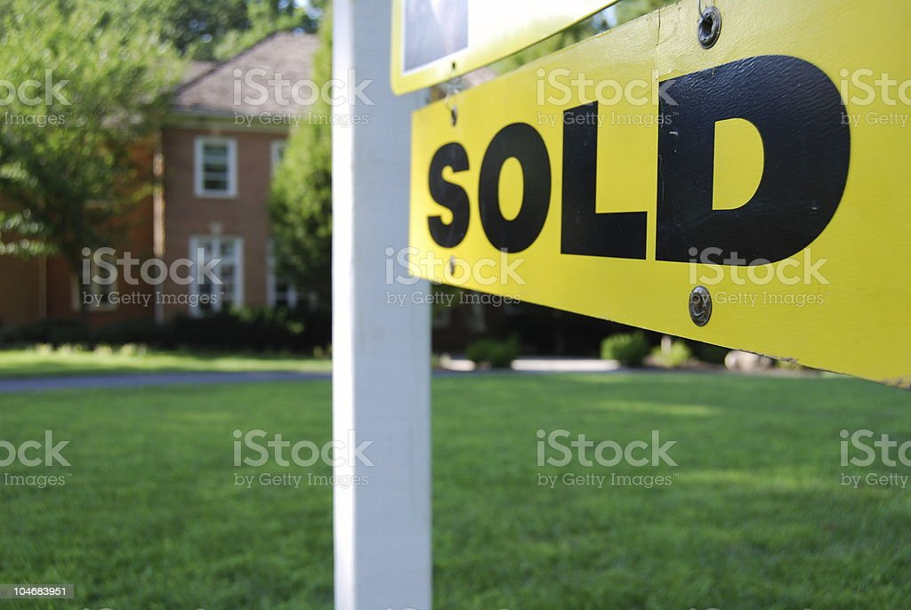 Sign saying sold in front of a house that was on sale stock photo