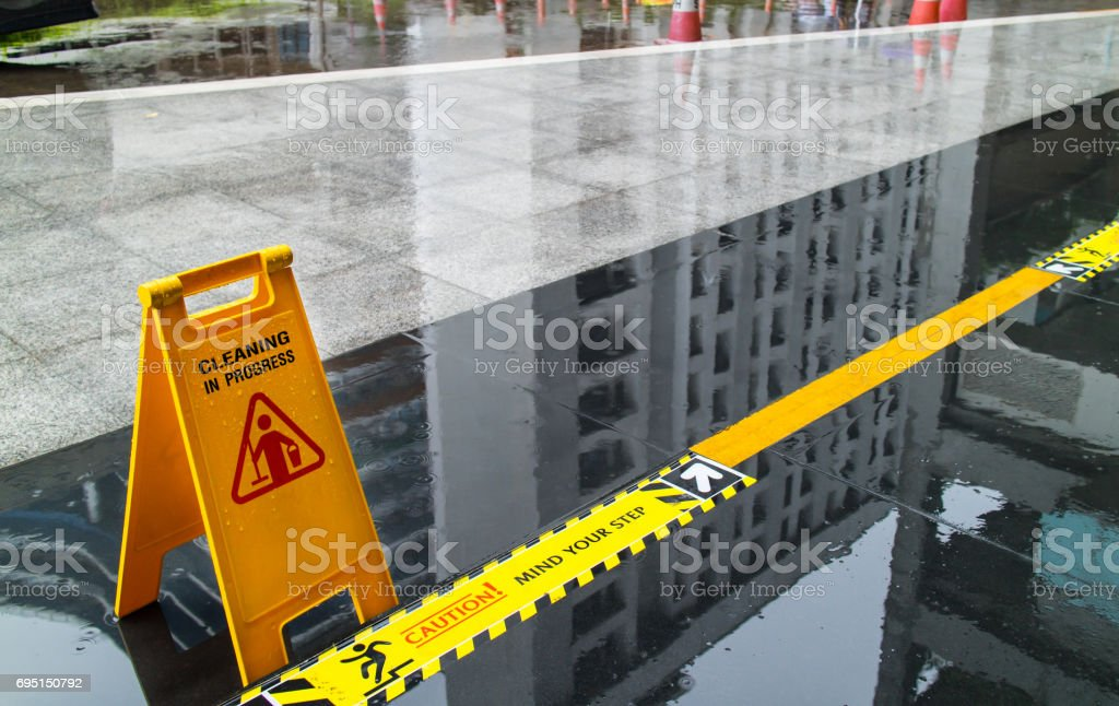 Sign showing warning of caution wet floor and mind the step in front of the building stock photo