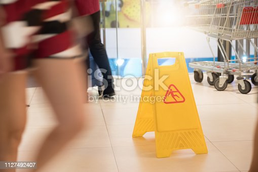 istock Sign showing warning of caution wet floor at airport. 1127492407