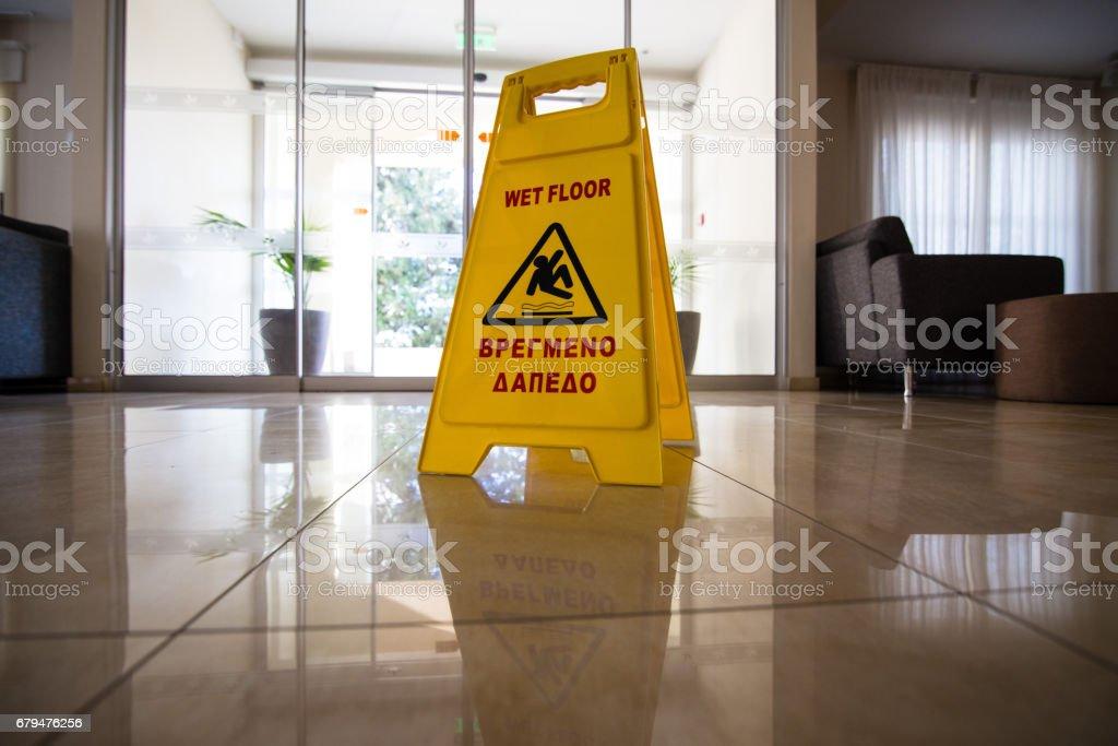 在日落的謹慎濕地板濕滑的瓷磚地板上警告標示顯示 免版稅 stock photo