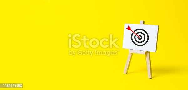 istock Sign stand with an arrow in the target on a yellow background. Hit exactly on center. Tactics of advertising targeting. advertise campaigns. Goal Achievement and Purposefulness 1182121190