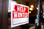 istock Sign text closeup for help wanted with red and white colors by entrance to store shop business building during corona virus covid 19 pandemic 1284290965