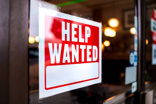 Sign text closeup for help wanted with red and white colors by entrance to store shop business building during corona virus covid 19 pandemic stock photo